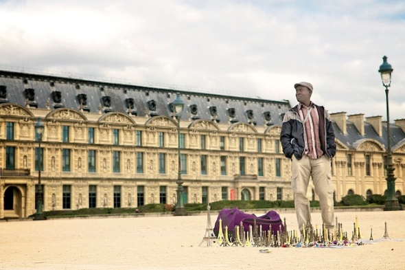 Man sells miniature Eiffel Tower statues in the park at the Louvre, Paris, France.